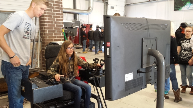 Southeast eighth grade student Hallie Plumley of Cherokee tries out the heavy equipment simulator at Careers in Construction.  The simulator was provided by Pittsburg State University.