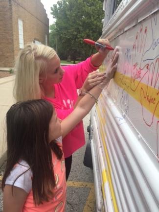 Senior Alex Rice assisting 3rd Grader Greenlee Webster